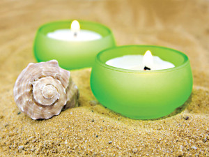 candle and sea shell on sand